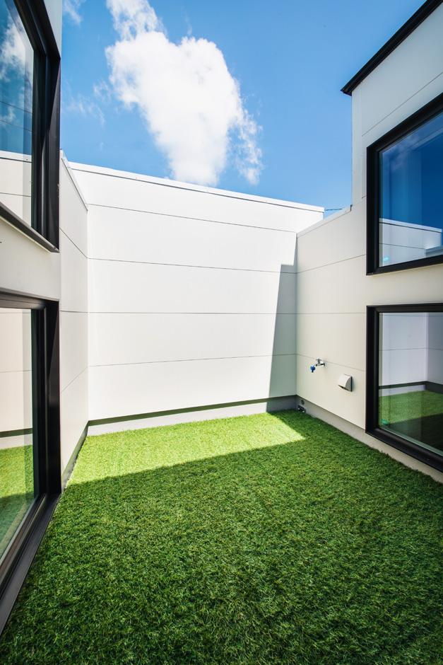 R+house 浜松中央(西遠建設)【趣味、建築家、1000万円台】壁を高くしてプライバシーを確保したバルコニー。人工芝を敷いて、自分たちだけのプライベート・ガーデンを実現。ダイニングと畳スペースに窓を設け、開放感を室内に取り込んだ