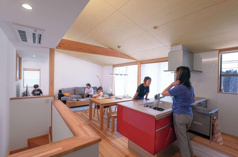 TANAKEN(田中建設)【子育て、自然素材、間取り】家族のコミュニケーションを育むオープンキッチン。長身の奥さまに合わせてワークトップを高めに設定。赤いキッチンパネルがナチュラルな空間のアクセントに