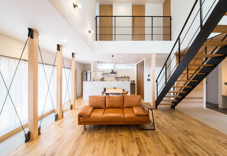 R+house 浜松中央(西遠建設)【デザイン住宅、子育て、建築家】大きな吹抜けで上下階が一体化したLDK 。家族が別々の場所にいても会話を楽しむことができ、コミュニケーションを深められる。窓の外にはウッドデッキがあり、フロアとデッキをつなぐ土間も確保した