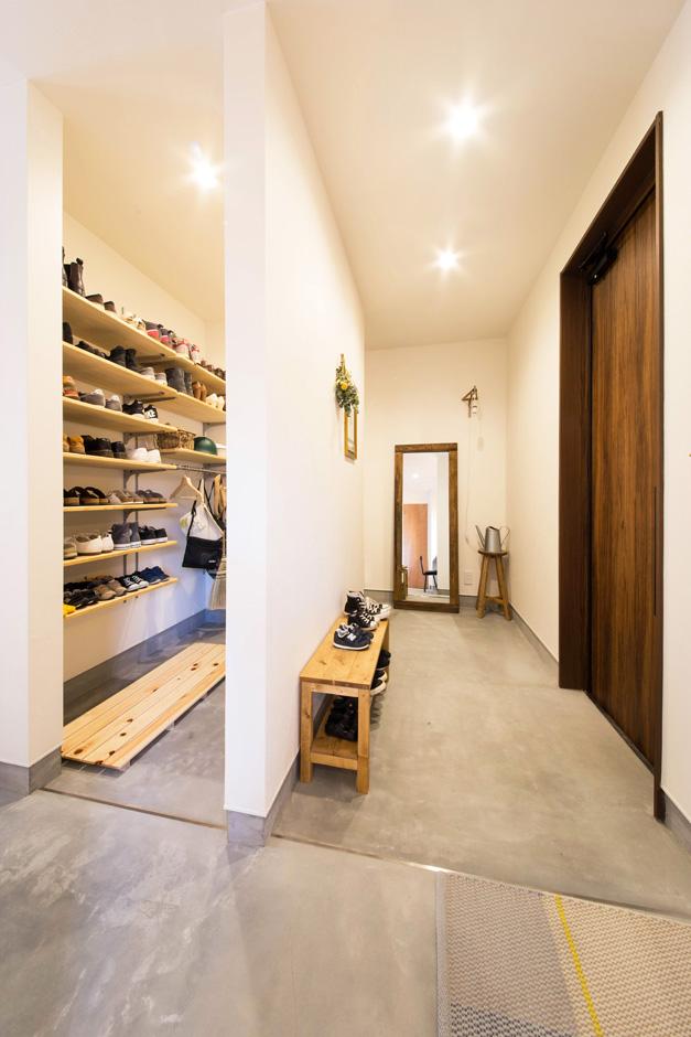 R+house 浜松中央(西遠建設)【デザイン住宅、子育て、建築家】玄関は壁で仕切って収納スペースをたっぷり確保。表玄関にはベンチを置いてドライフラワーを壁に飾り、おしゃれなカフェのように素敵な空間が出来上がり!