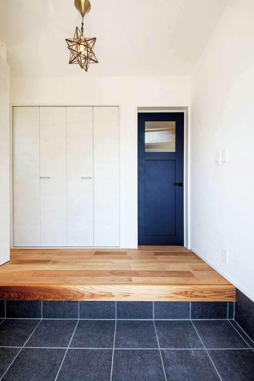 住たくeco工房【1000万円台、デザイン住宅、自然素材】白い空間にネイビーブルーのドアが映える玄関。正面の扉収納は、帰宅してすぐ着替えるのが習慣のご主人のために設けたクローゼット