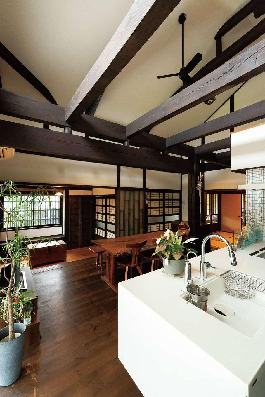 戸田工務店|古民家の大空間に現代的な白いアイランドキッチンが違和感なく融合している。リノベーションから8年が経過し、床も艶と味わいが出てきた