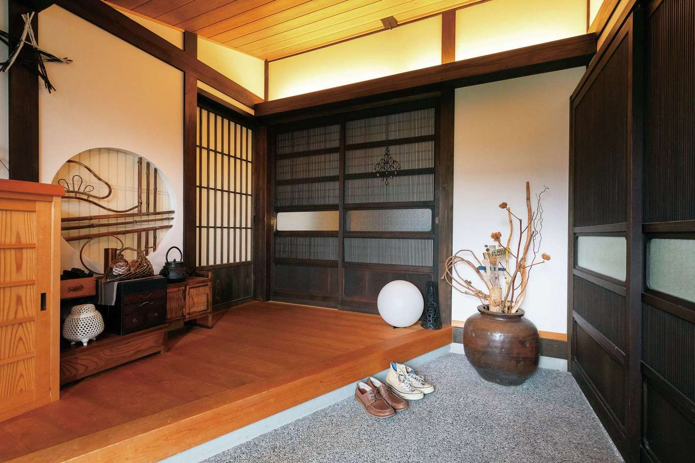 戸田工務店|高級旅館のような風情が漂う玄関ホール。洗い出し仕上げの土間と無垢の床、建具、古美術がバランス良く納まっている