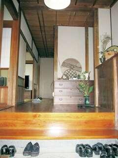 洗い出しの土間と框の段差を低くし、デザインや使い勝手を両立した玄関ホール。杉板の天井と間接照明がゲストを温かく迎える。竹細工をあしらった丸型のニッチは既存のまま、職人技が冴える千本格子の建具など、奥さまが集めてきた古道具と絶妙に調和している