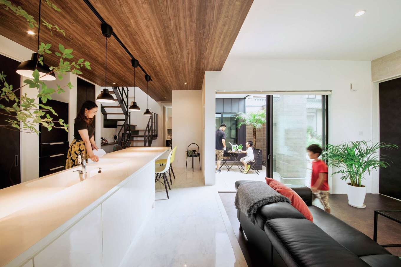 内田建設【デザイン住宅、間取り、建築家】中庭とリビングがつながることで、より開放的に感じられるLDK。リビングとキッチンの間に段差を設け、木目の折下げ天井でアクセントをつけた
