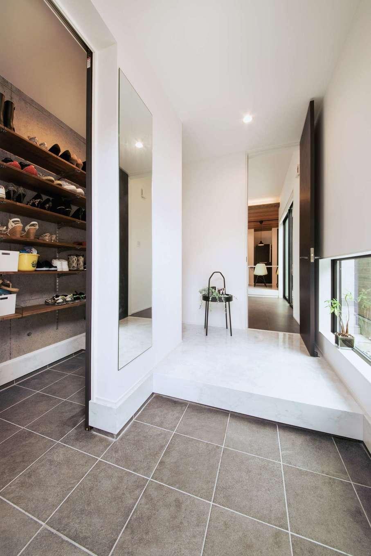 内田建設【デザイン住宅、間取り、建築家】床から天井まで届くハイドアを採用し、空間をより広く見せる玄関ホール