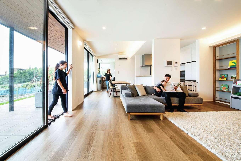 内田建設【デザイン住宅、趣味、間取り】東西に長いLDKは24畳の大空間。床から天井まで届く大きな開口部がリビングとテラスをフラットにつなぎ、より開放感が生まれた。高台立地で遠くの海が見渡せる