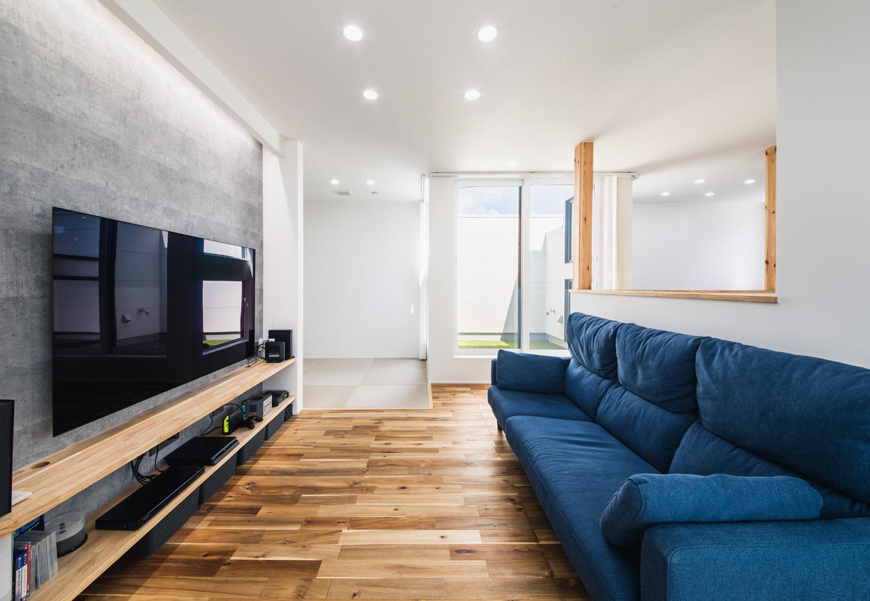 R+house藤枝(西遠建設)【1000万円台、趣味、建築家】夫妻がくつろぐリビングはゆとりの広さ。造作のT Vボードを壁一面に設け、大型テレビの前にベッド代わりにもなりそうな3人掛けのソファを置いてある。無垢のアカシアの床が素足に心地よい