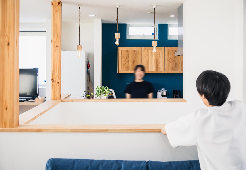 R+house藤枝(西遠建設)【1000万円台、趣味、建築家】吹抜けの階段ごしに、アイランドキッチンとリビングを向かい合わせに配置した間取りは、他の家にはなかなかないユニークなシチュエーション。程よい距離がそれぞれの空間に落ち着きをもたらしている。調理をしながら会話も楽しめる