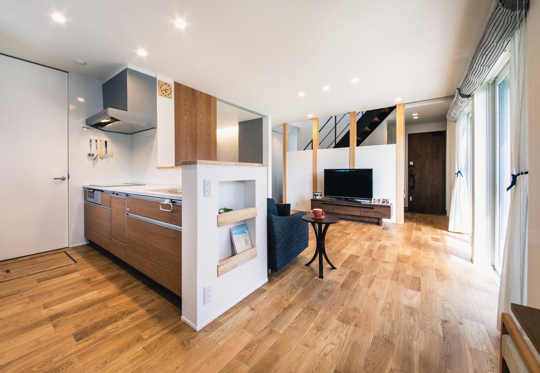 R+house藤枝(西遠建設)【省エネ、建築家、ガレージ】オープンキッチンからはフロア全体を見渡せる。ワークスペースにもゆとりがあるので、家族と一緒に調理や片付けができる。キッチンサイドの腰壁にはマガジンラックを設けてあり、料理の本や新聞などをすっきり収納