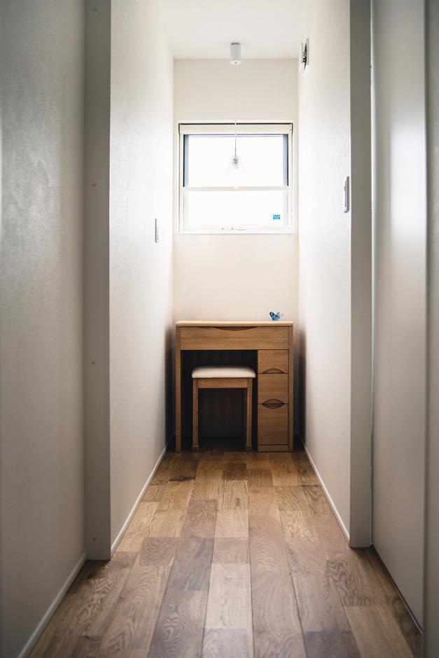 R+house藤枝(西遠建設)【省エネ、建築家、ガレージ】1階の洗面スペースとトイレの間に配置したのは、奥さまがお母さまから譲り受けた小机。マンション時代にも使っていたので、これからもずっと使いたいとの要望から、あらかじめ設計段階で置く場所を確保した。窓から自然光が入り、奥さまが毎朝ドレッサー代わりに利用