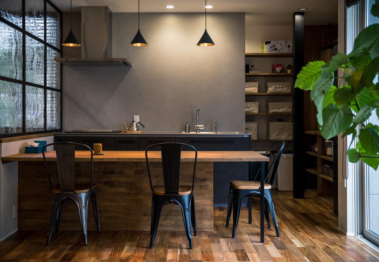 R+house藤枝(西遠建設)【デザイン住宅、建築家、インテリア】グレーの壁の微妙な色合いや素材感にまでこだわり、バーのように洗練されたダイニング空間が実現。黒いアイアンと無垢材が絶妙に調和し、心地よさをもたらしている