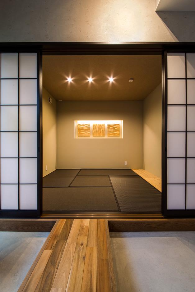 R+house藤枝(西遠建設)【デザイン住宅、建築家、インテリア】壁に木のパネルのオブジェを飾り、旅館の一室のように洗練された和室。ダイニングとの間に廊下を渡してある。障子を黒枠にしたことで、閉めたときの印象がインダストリアルなダイニングと違和感なく調和する