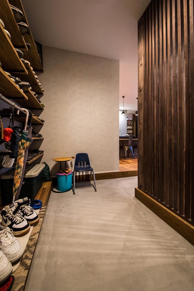 R+house藤枝(西遠建設)【デザイン住宅、建築家、インテリア】玄関には土間収納をたっぷり設けてある。オープンラックに靴を並べて、ハンガーパイプに服をかけ、見た目にもオシャレな収納が実現