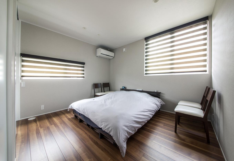 R+house藤枝(西遠建設)【デザイン住宅、建築家、インテリア】2階の寝室はシンプルで無駄のない空間。2方向に窓を設け、明るさと風通しに配慮した。道路に面した壁側は、周囲の視線に配慮して横長の窓を設置