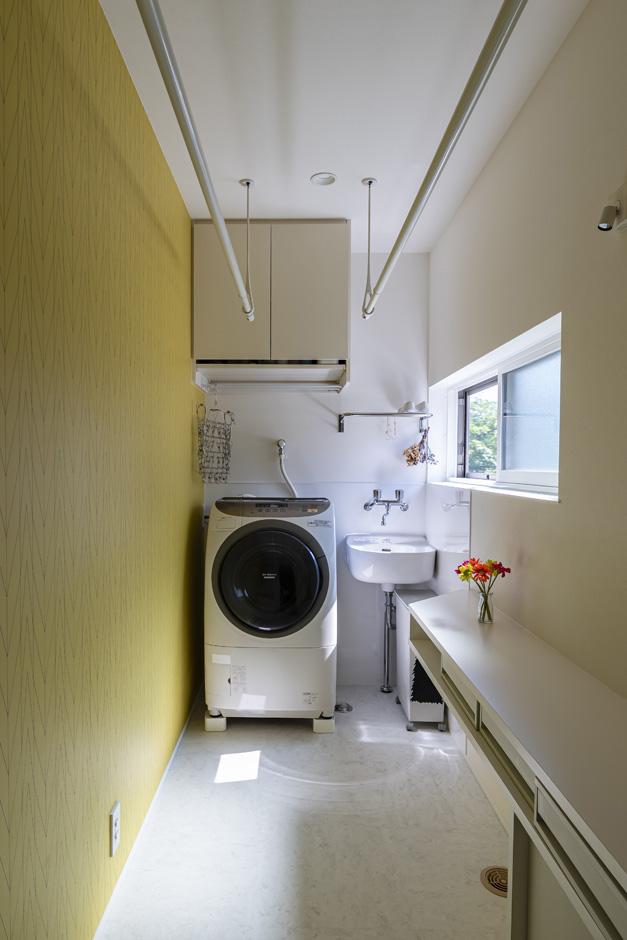 R+house藤枝(西遠建設)【デザイン住宅、間取り、建築家】勝手口とパントリーにつながるランドリー。家事カウンターや室内干し、水栓も設けてある。イエローのアクセントクロスを用い、デザイン性にもこだわった