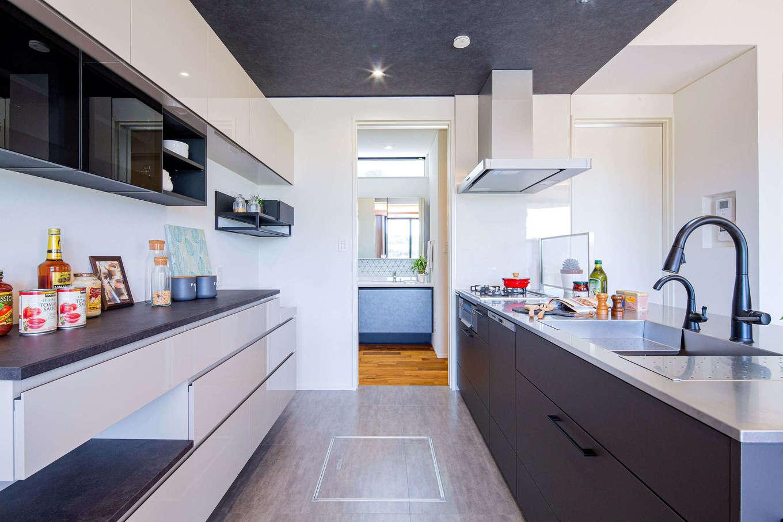 みずしまの家/水嶋建設【子育て、間取り、平屋】キッチンスペースは天井に黒い意匠をしつらえ、個性を演出。ワークスペースを広く取ったことで、大人が数人入っても窮屈に感じない。洗面室、脱衣室へ一直線につながる動線が共働き夫婦の家事時間を短縮