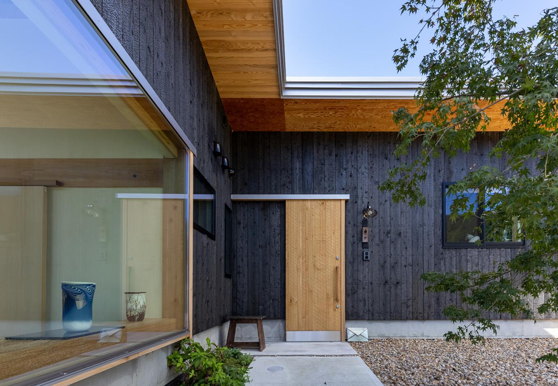 石牧建築【趣味、自然素材、平屋】ギャラリーの入口とは別に設けた住まい専用の玄関。名栗(なぐり)加工を施した木製のオリジナルドアは『石牧建築』の若い大工による渾身の作