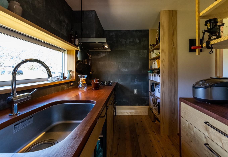 石牧建築【趣味、自然素材、平屋】クルーザーのキャビンを彷彿とさせる独立型のキッチン。窓から緑の景色を眺めながら調理できる。年季の入ったフライパンやコーヒーメーカーなどの調理器具はキャンプでも使っている