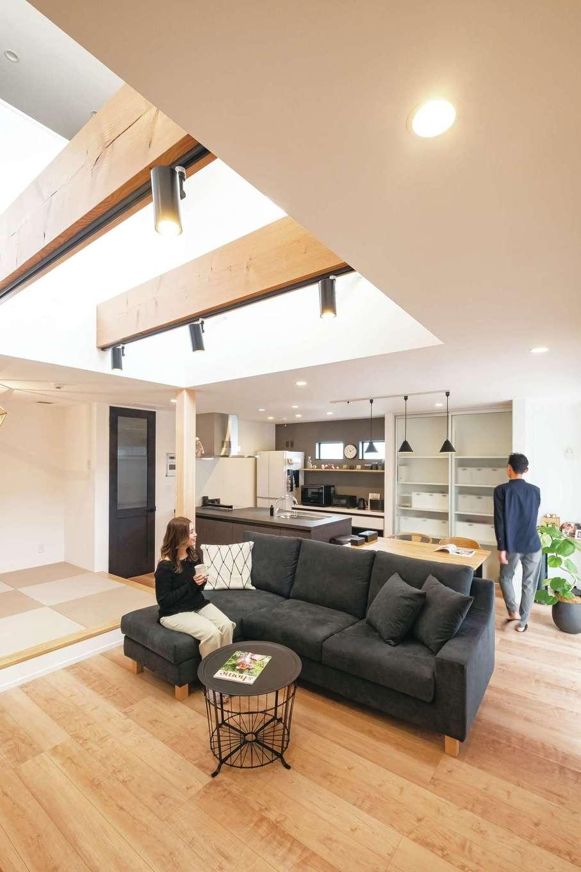 イデキョウホーム【デザイン住宅、省エネ、インテリア】吹抜けの開放感が気持ちいいLDK。視界がタテ・ヨコに抜けていくので、実面積よりも広く感じられる。ソファに座ってウッドデッキ、庭を眺めるのが夫婦にとって至福のひととき。全館空調と吹抜けとの相性も抜群で、家庭用のエアコン1台で家中隅々まで温度差がなく快適に過ごせる