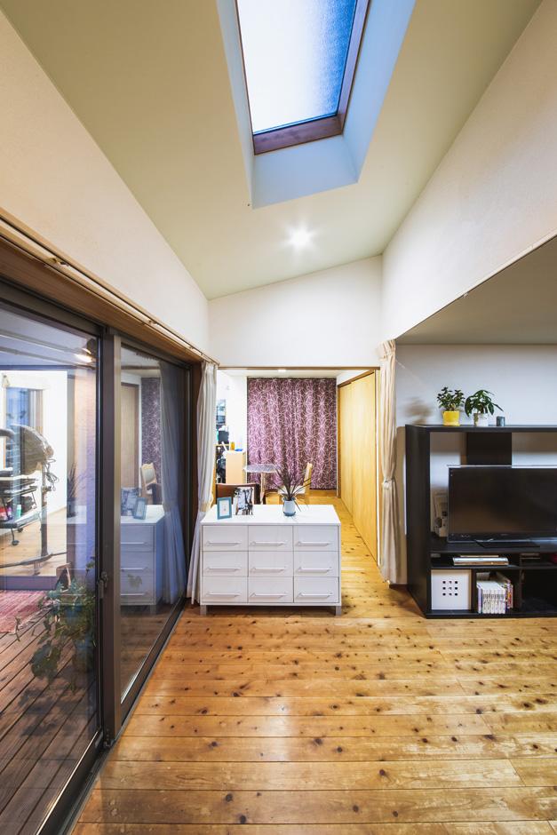 入政建築|LDKと自宅ヘアサロンはドアを開けると一続きに。天窓のある勾配天井から注ぐ光、経年美が加わったヒノキの床、漆喰の壁が織りなす自然な色合いが心地いい。夜はここが夫婦の寝室になるが、「耐震補強のおかげで車が通っても揺れなくなりました(笑)」そうお二人は笑う