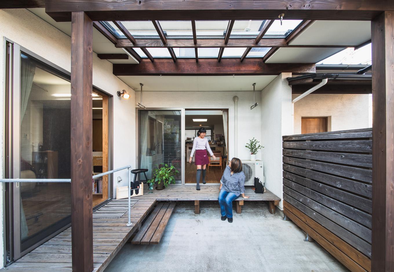 入政建築|2010年のリノベーションでは、庭全体を覆うほど広く仕上げたウッドデッキ。自宅サロン改修の際、美容院へのアプローチ階段を造るべくデッキ部分を減築した。同時に土間と屋根を拡張したおかげで「BBQがやりやすくなりました」とTさん