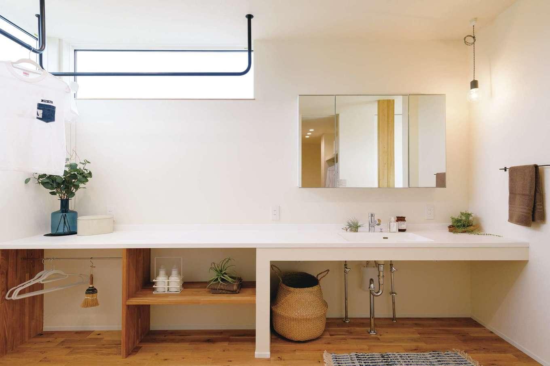 住家 ~JYU-KA~【デザイン住宅、間取り、建築家】共働きの奥さまにとって、室内干しのスペースは念願。脱衣場に隣接するのは、ウォークインクローゼットを一体化した、広い洗面台のある日当たりのいいランドリールーム。浴室を2階にすることで、便利な洗濯動線が可能に