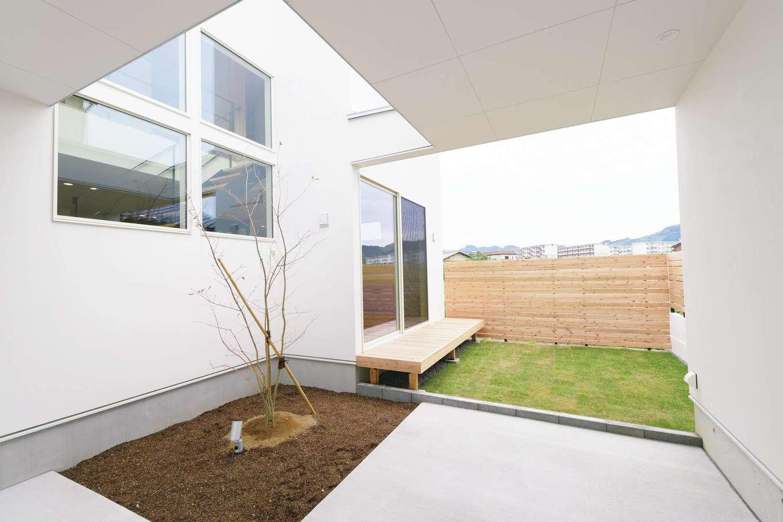 住家 ~JYU-KA~【デザイン住宅、間取り、建築家】駐車場から中庭を臨む。周囲をウッドフェンスで囲み、隣接する住宅からの視線も気にならない工夫が