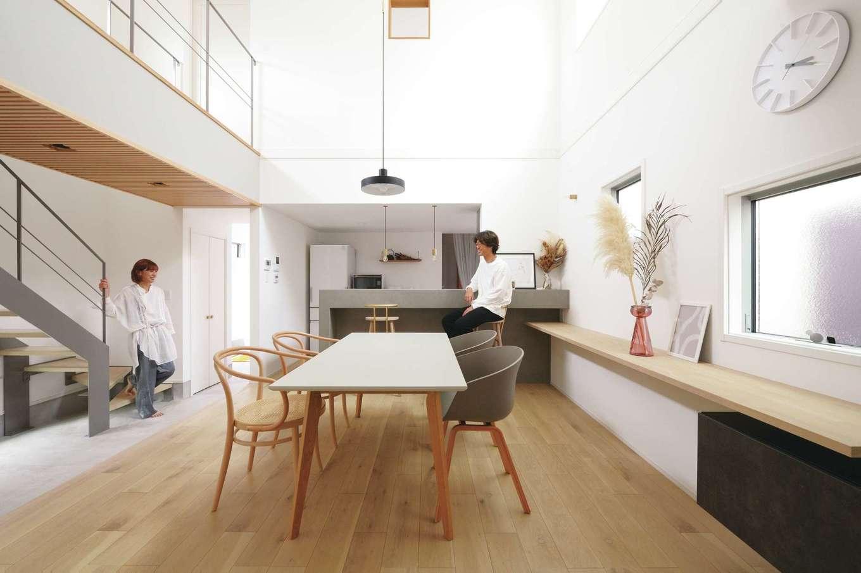 ハートホーム【デザイン住宅、趣味、間取り】白・グレー・木目でコーディネートしたLDK。高い吹抜けの窓からたっぷりの光が降り注ぎ、心地いい住空間を実現。家具、照明、雑貨のセレクトも夫婦のセンスを感じさせる