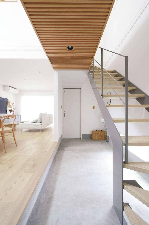 ハートホーム【デザイン住宅、趣味、間取り】玄関から一直線に続くコンクリートの土間。グレーの鉄骨階段と木目の空中廊下が絶妙に調和している