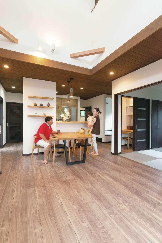 三和建設【デザイン住宅、子育て、間取り】天井にも無垢の木材をあしらったLDK。キッチンの天板やダイニングの飾り棚には一枚板を使用。間接照明の明かりも効果的で、モダンでシックなインテリアの中にも、自然の優しさを感じる温かみのある空間に仕上がっている。各部屋はすべてリビングにつながる設計で、フロア全体が広々とした印象