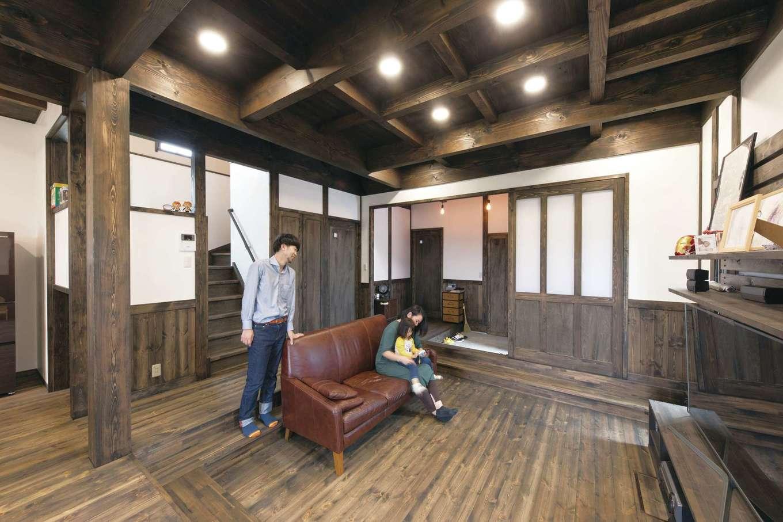 東海ハウス【子育て、和風、間取り】床材と同じパイン材の腰壁と漆喰が、時を経た古民家の雰囲気をまとうリビング。仕切りがない分、掘り込みを採用して空間を仕切っている