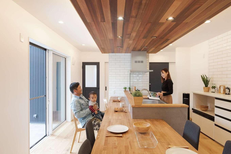 KureKen 榑林建設【デザイン住宅、省エネ、間取り】中央に配されたキッチンには帰宅の気配や庭で遊ぶ姿、和室でのお昼寝の様子も届く。ダイニングテーブルは分離可能。家族の成長や来客にあわせレイアウトできる。奥に用意された浴室、ランドリールーム、ファミリークローゼットと続く洗濯動線も家事効率を高めている。キッチン側面のモールテックスはクールな表情が持ち味。無垢、漆喰、タイル、アイアンといった素材がバランスよく採り入れられ、洗練とぬくもりが調和する空間に仕上がった