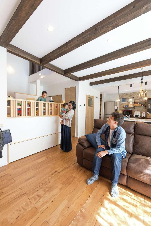 小玉建設【子育て、自然素材、スキップフロア】掃き出し窓と階段の吹き抜けからたっぷり光が入る、明るく開放的なリビング。構造材の梁の一部を現しに。天井が高くなり、白い天井に深みのある色の化粧梁で古民家のようなぬくもり感を演出。床材は洋風な雰囲気に合うサクラを選択。スキップフロア下は収納として活用し、今は子どものおもちゃ入れになっているそう