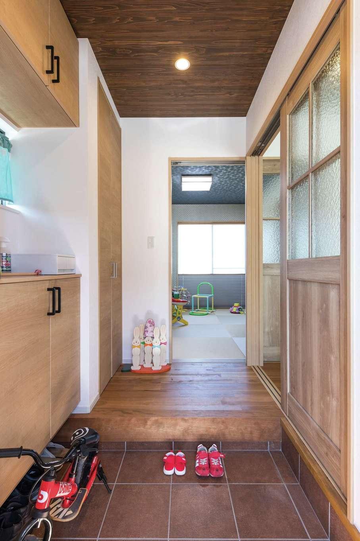 小玉建設【子育て、自然素材、スキップフロア】天井に杉板を貼り、木のぬくもりに迎えられる玄関。靴収納に加えて天井まで届く大きな収納も作った。奥はリビングを通らずに来客を通せる和室
