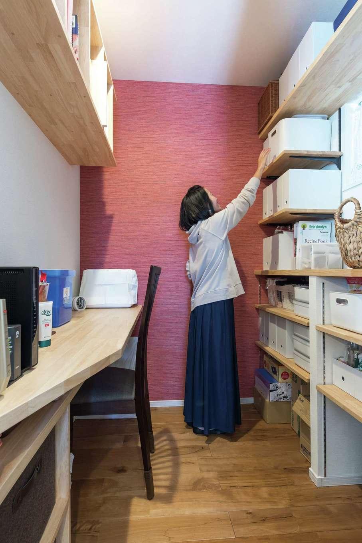 小玉建設【子育て、自然素材、スキップフロア】「キッチンで料理をしているとき、例えば鍋を火にかけている間にちょっと何かできれば」という奥さまのイメージに沿って、キッチンの真横に作られたママクローク。パントリーを兼ねているため、向かって右側に食材保管用の棚、左側に書き物や作業をするカウンターと本棚を設けてある。「小さくても自分だけのスペースがあるのがすごく気に入っています」と奥さま。アクセントクロスはじっくり検討して自分の好きな色柄を選んだそうだ