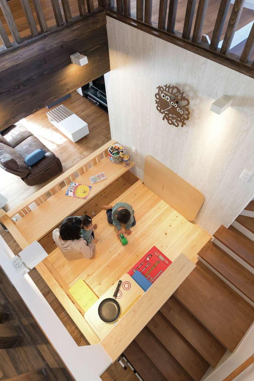小玉建設【子育て、自然素材、スキップフロア】子どもの遊び場としてHさん夫妻が最初から希望していたスキップフロア。すべてヒノキで造り、木の香りが漂う。リビング階段にしたかったこともあり、『小玉建設』からの提案で吹き抜けと組み合わせ、階段の途中に作ることに。今ではすっかり長男のお気に入りスペースになっているそうだ。いずれは大人が腰かけて使えるようにと、カウンターの下は足を入れられる仕様。今は子どもが使いやすいようにぴったり閉じるふたをしてある