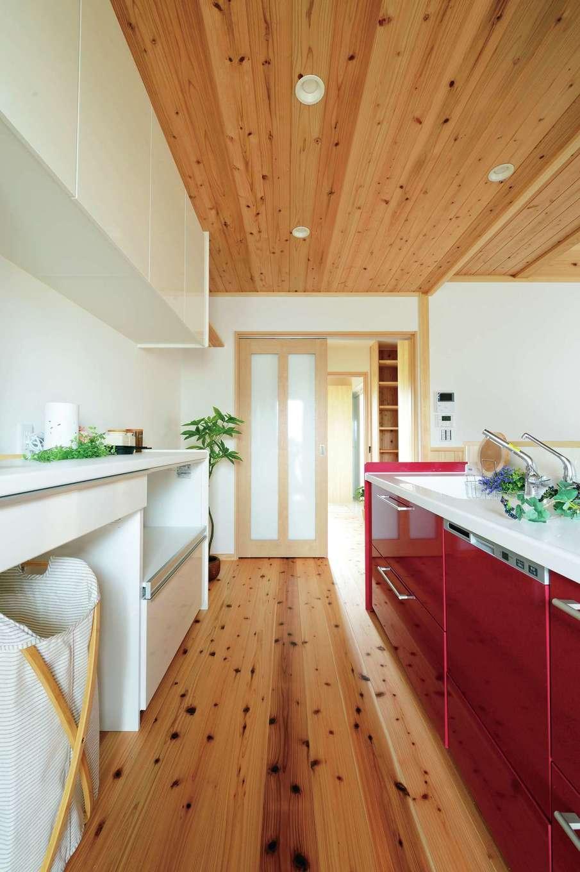 村木建築工房【和風、自然素材、平屋】木目に引き立つ赤いシステムキッチン。背面には収納もたっぷり設けてある
