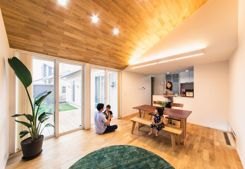 子育て安心住宅【自然素材、平屋、ガレージ】板張りの勾配天井が開放的なLDK。照明はダウンライト、カーテンはバーチカルブラインドを採用し、すっきりとした清潔感のあるインテリアで統一
