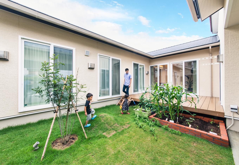 子育て安心住宅【自然素材、平屋、ガレージ】周囲に気兼ねなくくつろげる芝生の中庭。ご主人のD I Yによるレンガ造りの家庭菜園では、トマトやホウレンソウ、ナス、トウモロコシと、多彩な野菜を収穫できた。子どもと一緒に育て、収穫し、料理して食べる楽しさを体験でき、食育にも役立っている
