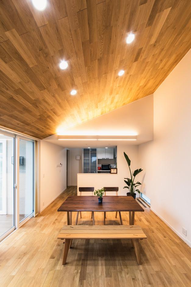 子育て安心住宅【自然素材、平屋、ガレージ】間接照明に照らされて、勾配天井の木目がゆたかな表情をもたらすダイニング。掃出窓を天井いっぱいの高さまで設けたことで、無駄なラインのない洗練されたデザイン空間が実現。いっそう開放感が強調されている