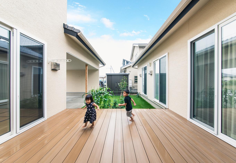 子育て安心住宅【自然素材、平屋、ガレージ】ウッドデッキはLDKと子ども部屋、和室の3部屋と繋がっている。子どもたちがデッキを介してあちこちの部屋を行き来し、のびのびと遊ぶことができる