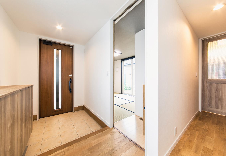 子育て安心住宅【自然素材、平屋、ガレージ】シンプルで落ち着きのある玄関。ホールに上がってすぐの場所に和室を設けてある