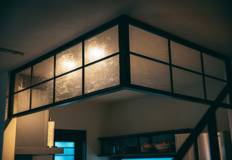 バルハウス【和風、自然素材、インテリア】キッチンの垂れ壁の代わりに、アイアンの枠にガラスを貼ったオリジナルのパーティションを採用。曇りガラスに照明の灯りがほんのり透けて、大正浪漫の情緒を醸し出す