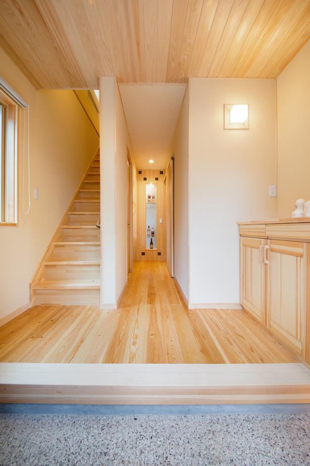 瀧口建設 洗い出しの土間と珪藻土の壁、無垢の床と天井が美しく調和した、端正な玄関。玄関収納とオープンラックを設け、靴やアウトドア用品などをすっきりとしまい込める