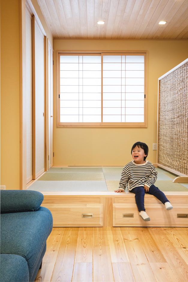 瀧口建設 リビングに設けた小上がりの畳コーナーは、子どもたちの遊び場や家族の団らんスペースとして大活躍。床下の引き出しは1間分の奥行きがあり、荷物をたっぷり収納できる。リビングとの仕切りには、同社オリジナルのヨシズの衝立を利用