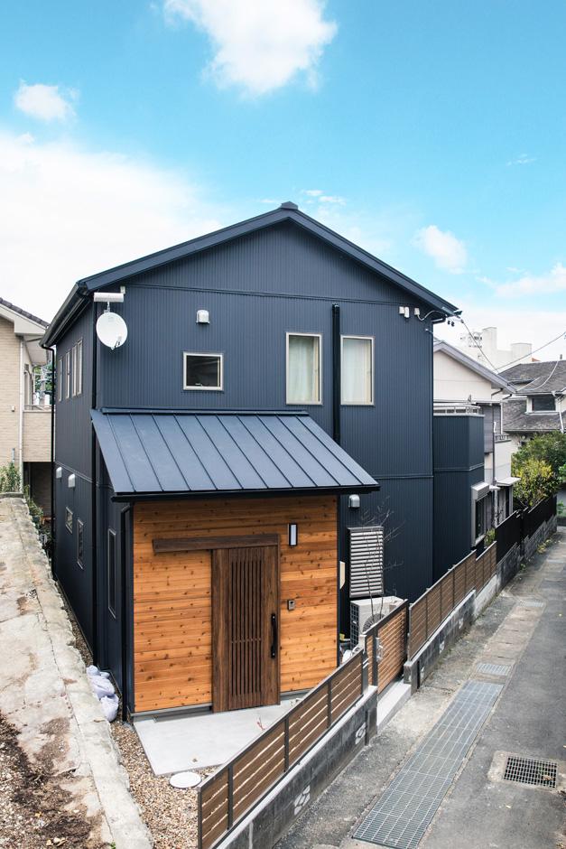 瀧口建設 耐震性を考慮して、瓦の屋根をガルバリウム鋼板に変更。外壁にも耐久性にすぐれたガルバリウム鋼板を採用した。濃いグレーの外壁にレッドシダーの無垢板張りをアクセントに加え、個性と上質感を強調