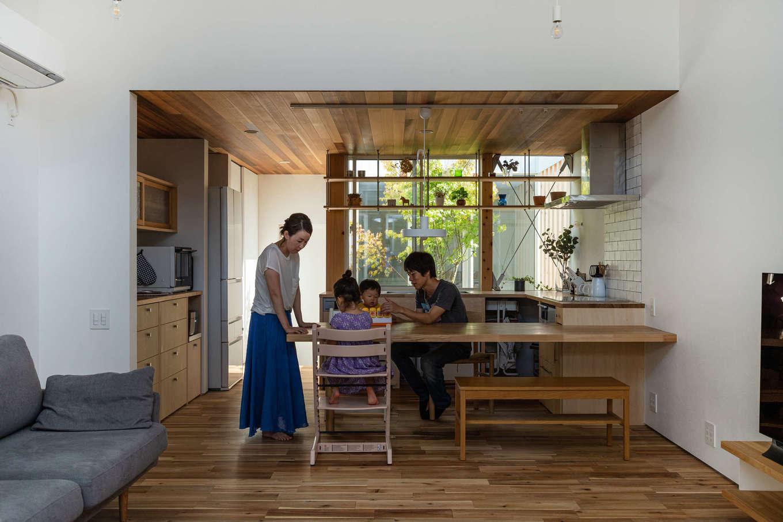 NATUREスペース【狭小住宅、建築家、平屋】ダイニングテーブルをキッチンと一体化することで、家事と団らんの距離が近づく。キッチンの北向きの窓には、奥様お気に入りの造作飾り棚。好きなものを飾ることができる
