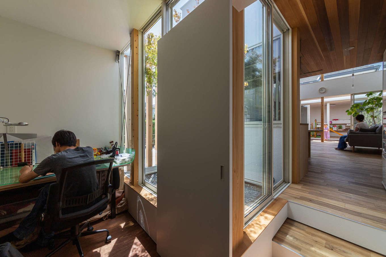 NATUREスペース【狭小住宅、建築家、平屋】仕事部屋とLDKのつながり。仕事部屋の横には、植栽、砂利敷きの中庭を設けており、また居住スペースよりも床を下げることで、空間をさりげなく仕切っている