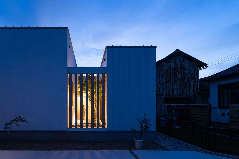 """NATUREスペース【狭小住宅、建築家、平屋】木格子の奥の中庭から漏れ光る灯りや、植栽のシルエットが美しい外観。右側が仕事場の""""箱""""、左側がLDKの""""箱""""で、中庭を介して繋がっている"""